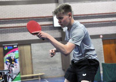 Boy in grey tshirt playing table tennis
