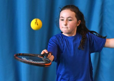 Girl bouncing tennis ball on racket