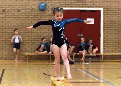 Gymnastics little girl on bench