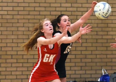 Two teenage girls competing for netball