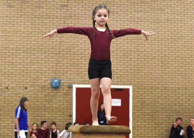 Young girl gymnast balancing on horse bench