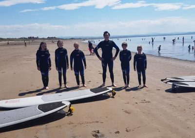 Kids on the beach with coach and surf boards